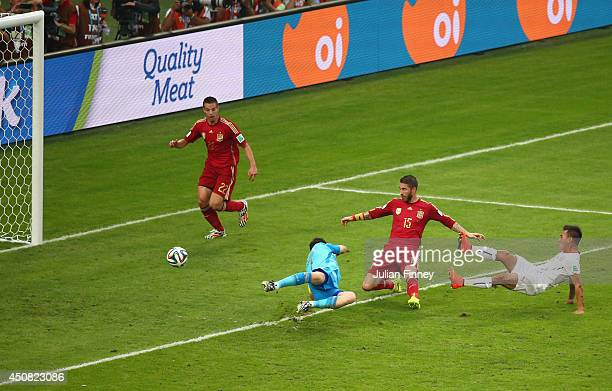 Eduardo Vargas of Chile shoots and scores his team's first goal past Sergio Ramos and goalkeeper Iker Casillas of Spain during the 2014 FIFA World...