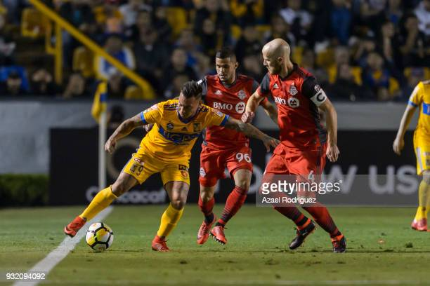 Eduardo Vargas of Tigres fights for the ball with Auro Junior and Michael Bradley of Toronto during the quarterfinals second leg match between Tigres...
