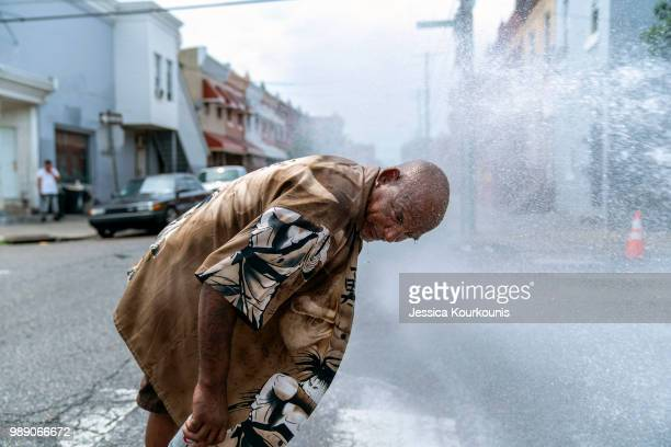 Eduardo Velev cools off in the spray of a fire hydrant during a heatwave on July 1 2018 in Philadelphia Pennsylvania An excessive heat warning has...