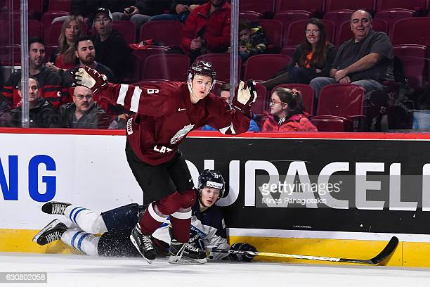 Eduards Tralmaks of Team Latvia takes down Henrik Borgstrom of Team Finland during the 2017 IIHF World Junior Championship relegation game at the...