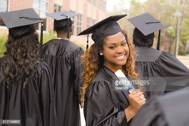 education: african descent female graduate and friends on college campus. - graduation gown stock pictures, royalty-free photos & images