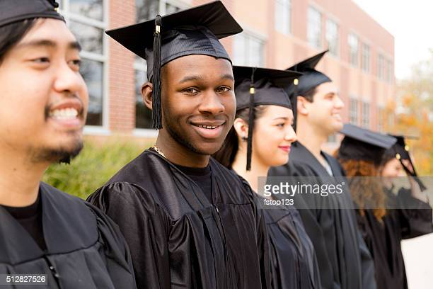 education: african descent male graduate and friends on college campus. - graduation gown stock pictures, royalty-free photos & images