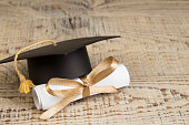 education concept. Graduation hat with gold tassel, scroll on the on a wooden table. Law concep- with copy space for your ad text.