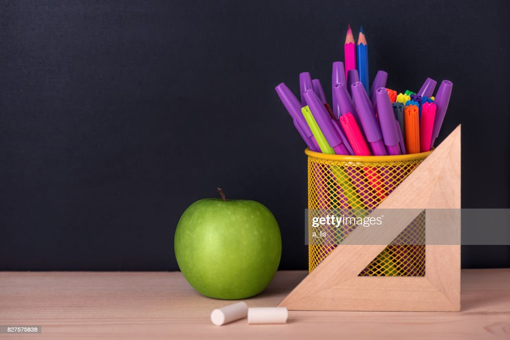 Education Concept With Green Apple Ruler Or Triangle Felt Pens Chalks Over Black