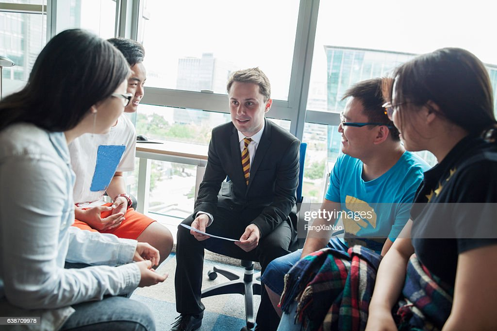 Education consultant with Chinese students in office : Stock Photo