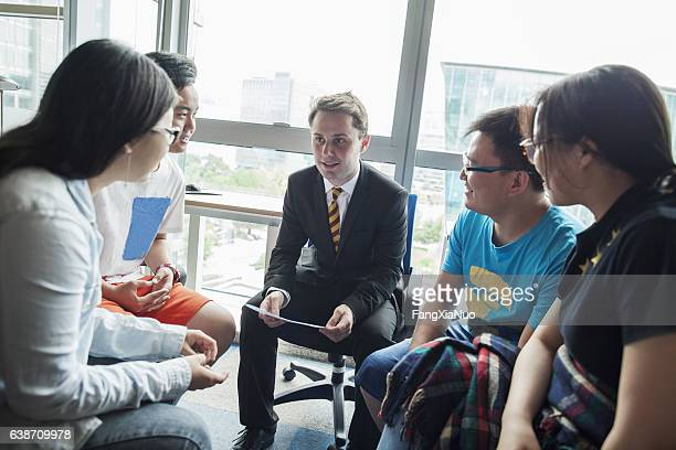 education consultant with chinese students in office - college application stock photos and pictures