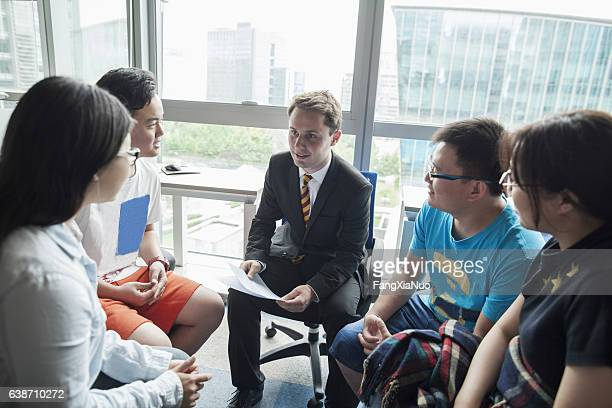 Education consultant with Chinese students in office