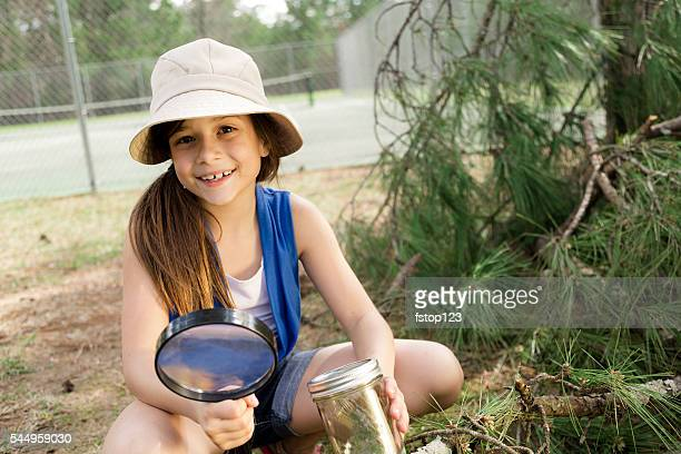 Education: Cute little girl with magnifying glass at park. Science.