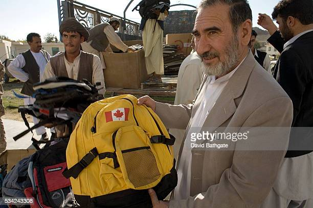 Education Director for Kandahar Province, Hayatullah Rafiqi, gratefully displays backpacks filled with school supplies donated by Canadian forces...