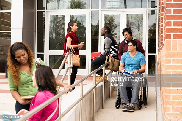 education: disabled student helped down wheelchair ramp. college campus. - accessibility stock pictures, royalty-free photos & images