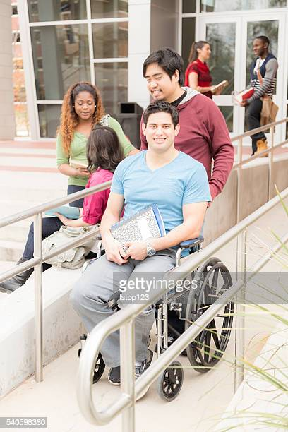 education: disabled student helped down wheelchair ramp. college campus. - paraplegic stock photos and pictures