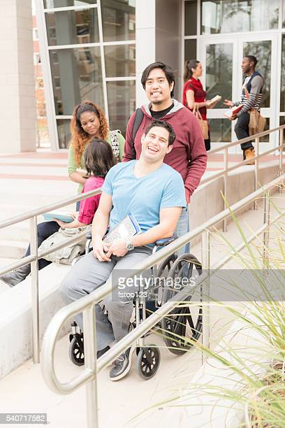 education: disabled student helped down wheelchair ramp. college campus. - disabled access stock photos and pictures