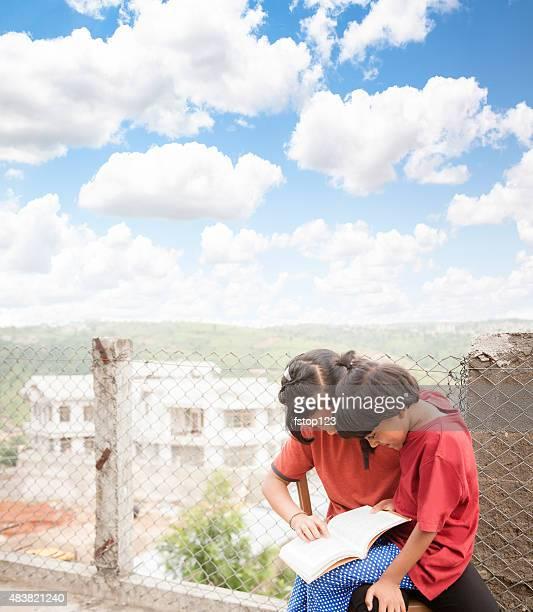 Education. Indian descent children studying, homework outdoors.