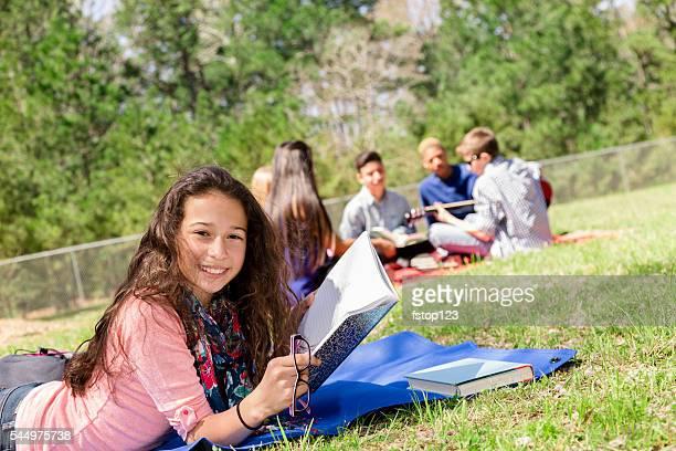 La educación : Latina los estudios de Chica adolescente en parque local. Amigos de fondo.