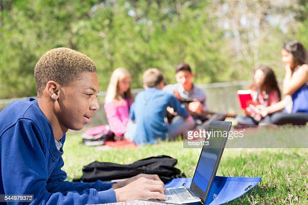 Education: Mixed-race teenage student studies using laptop outdoors.  Campus, park.