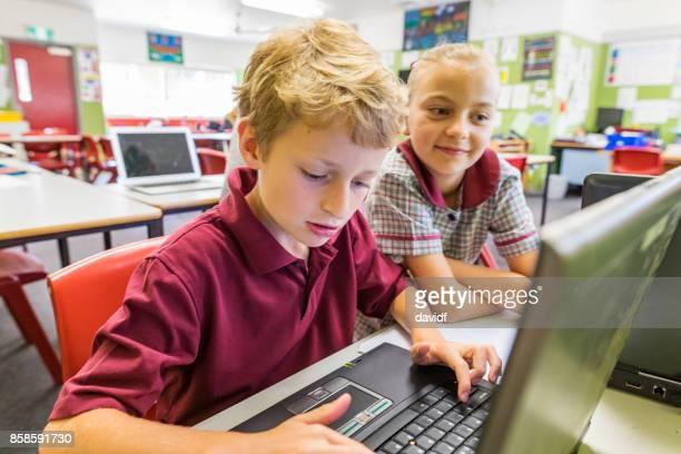 コンピューターを使用して小学生の教育 - 男子生徒 ストックフォトと画像