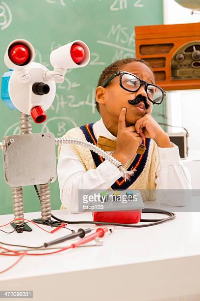 Education:  Retro revival boy making robot in science lab.