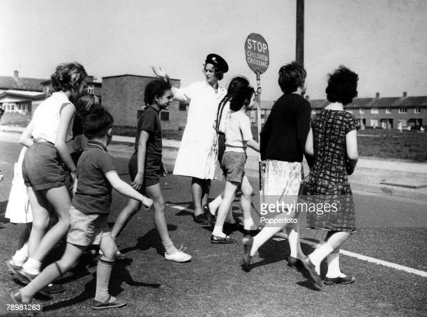 circa 1950's A school crossing patrol with the attendant assisting children to safely cross the road