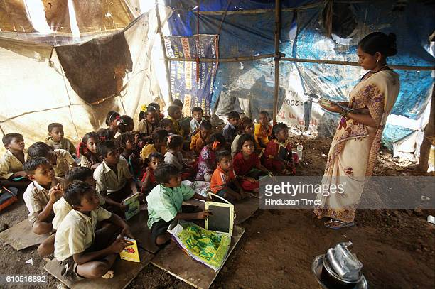 Education School for Ragpickers Children Kavita Sopane teaches the children of ragpickers the alphabet in their makeshift classroom in Durgawadi slum...
