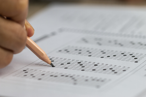 Education school test concept : Hands student holding pencil for testing exams writing answer sheet or exercise for taking fill in admission exam multiple carbon paper computer at university classroom 1152410679