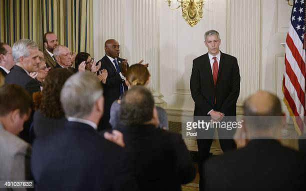 Education Secretary Arne Duncan receives a standing ovation after announcing that he will step down during a news conference with President Barack...