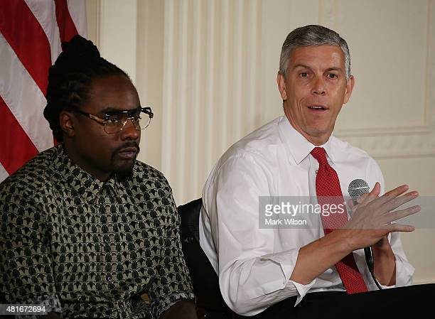 Education Secretary Arne Duncan speaks while musical artist Wale listens during a discussion on higher education in the East Room of the White House...