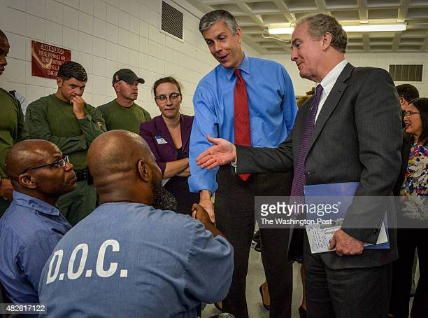 Education Secretary Arne Duncan, top center, and Rep. Chris Van Hollen greet inmates enrolled in an education program at a local prison on July 2015...