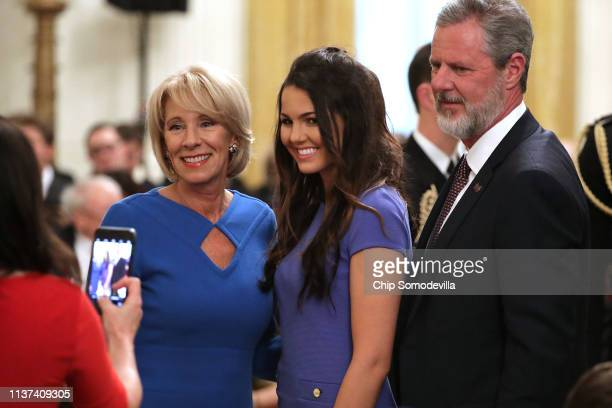 S Education Secretary Betsy DeVos and Liberty University President Jerry Falwell pose for photographs before President Donald Trump signs an...