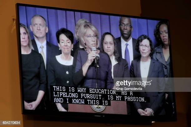 Education Secretary Betsy DeVos appears on a television screen with closed captions while delivering remarks to employees during her first day on the...