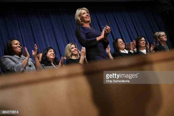 Education Secretary Betsy DeVos joins employees on stage during her first day on the job at the Department of Education February 8 2017 in Washington...