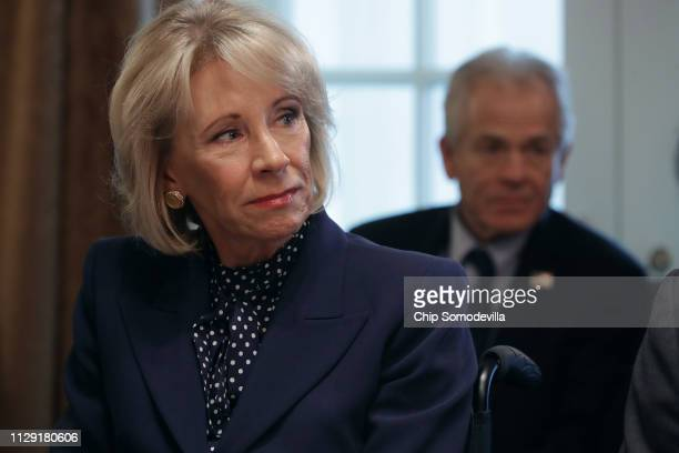 Education Secretary Betsy DeVos listens to US President Donald Trump talk to reporters during a cabinet meeting in the Cabinet Room at the White...