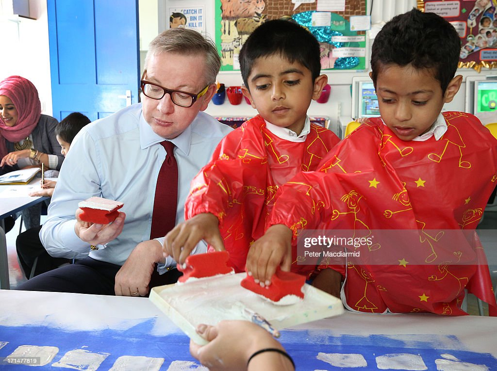 Education Secretary Michael Gove holds a paint sponge as he helps paint a picture of Canary Wharf during a visit to Old Ford Primary School on June 25, 2013 in London, England. Tomorrow Mr Osborne will announce the Government's spending review for 2015-1016. Earlier the Chancellor announced that spending on schools will be ring fenced.