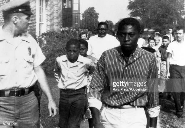 3rd September 1957 Greensboro North Carolina Black students escorted by a policeman calmly pass a crowd of whites opposed to their integration at...