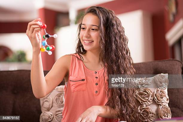 Education.  Teenage girl studying DNA molecule, science at home.
