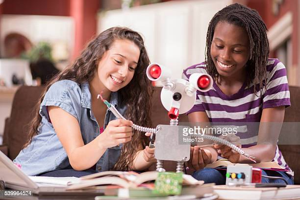Education.  Teenage girls studying science, engineering at home. Homework.