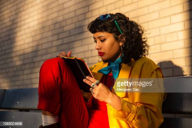 young woman writing on notebook at sunset in park - lgbtq  female stock pictures, royalty-free photos & images