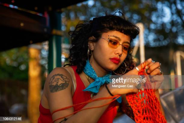 young woman knitting in park - knitting stock pictures, royalty-free photos & images