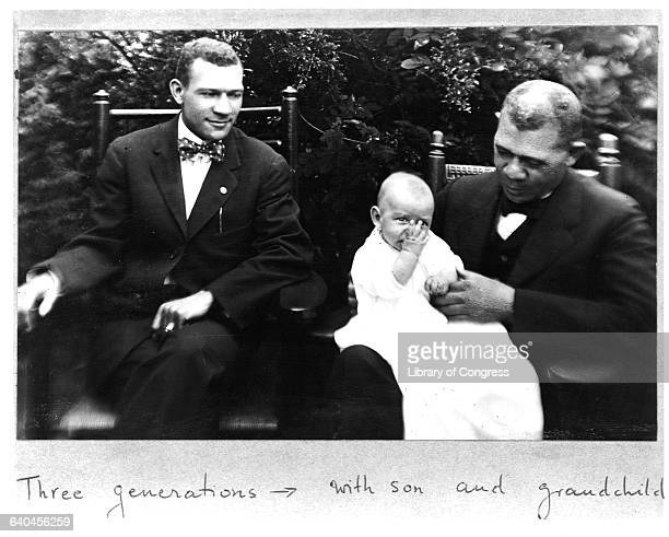 Educator Booker T Washington sits with his son holding one of his grandchildren
