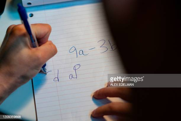 Educator Scott Slivken writes backwards so his students can read his writing over webcam as he helps his students solve math problems as he holds...