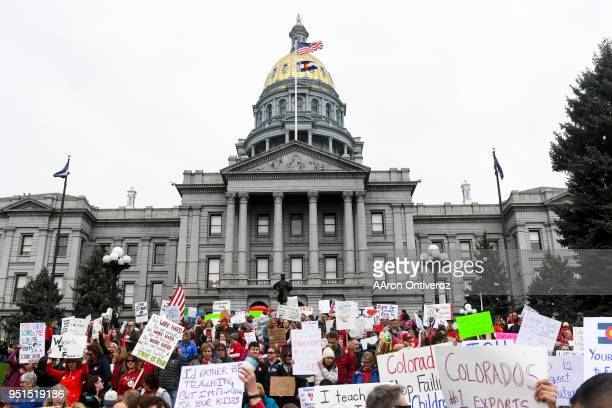 Educators gather en masse wearing red and holding signs during a teachers rally for more educational funding at the Colorado State Capitol on...