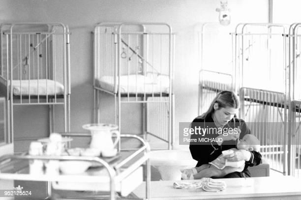 Educatrice faisant manger un bébé dans le dortoir d'une crèche à Créteil en 1979 dans le ValdeMarne France