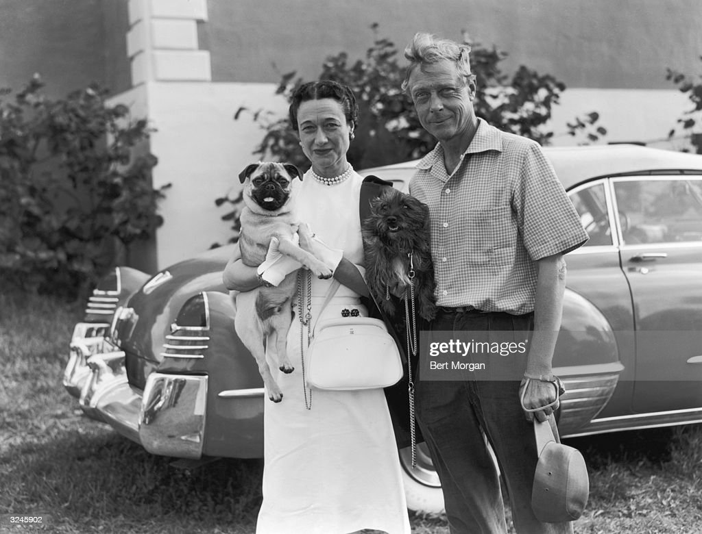 Edward (1894 - 1972) and Wallis Simpson (1896 - 1986), the Duke and Duchess of Windsor, pose with their dogs, a pug and a terrier, in front of a car outside the Seminole Club in Palm Beach, Florida. The Duchess is wearing pearls with a white dress, gloves, and purse. The Duke is wearing a short-sleeved shirt and pleated pants.