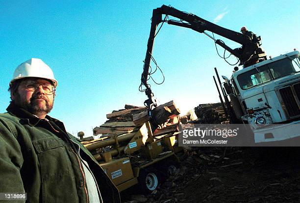 Edward App stands in front of a Log Buster December 13 2000 which splits large logs into shorter pieces to be then cut into firewood at App Tree Inc...