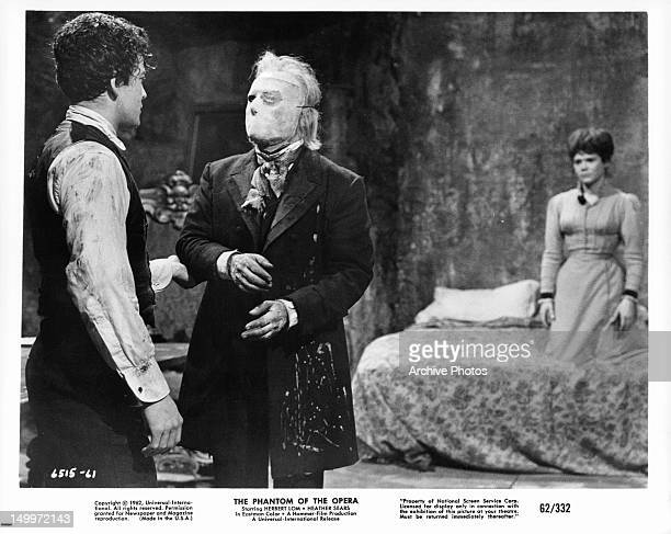 Edward de Souza grabs the arm of Herbert Lom with Heather Sears in the background in a scene from the film 'The Phantom Of The Opera' 1962