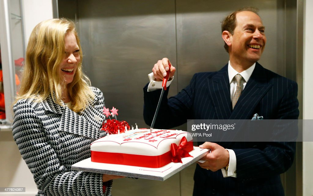 Edward, Earl of Wessex cuts his birthday cake held by Hannah-Polly Williams of London's Air Ambulance during a visit to the London Air Ambulance at the Royal London Hospital on March 10, 2014 in London, England.