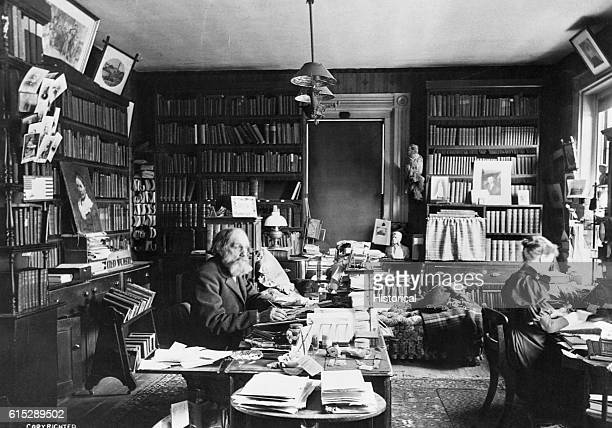 Edward Everett Hale sits at a desk in a booklined study while a woman works at a desk Hale was the chaplain of the United States Senate and the...