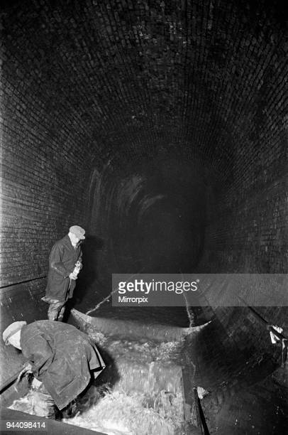 Edward Farmer and his gang seen here underground cleaning scraps of paper and anything likely to cause obstruction in the culvert under Central...