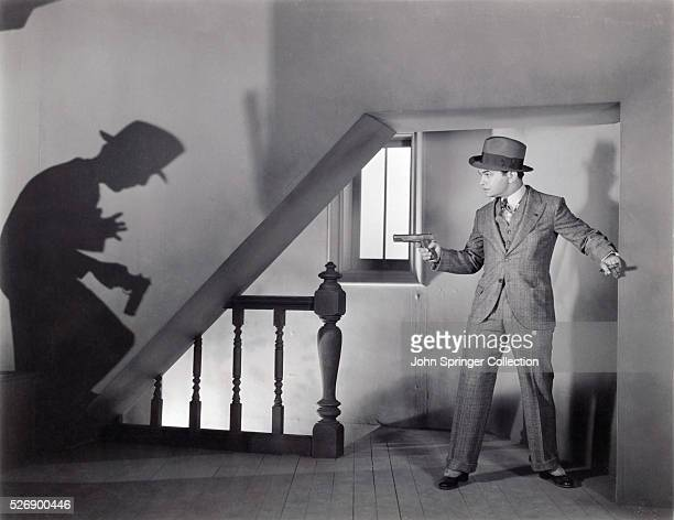 Edward G Robinson as Cesare Enrico Bandello points a gun at a shadow of a man he just shot in Little Caesar