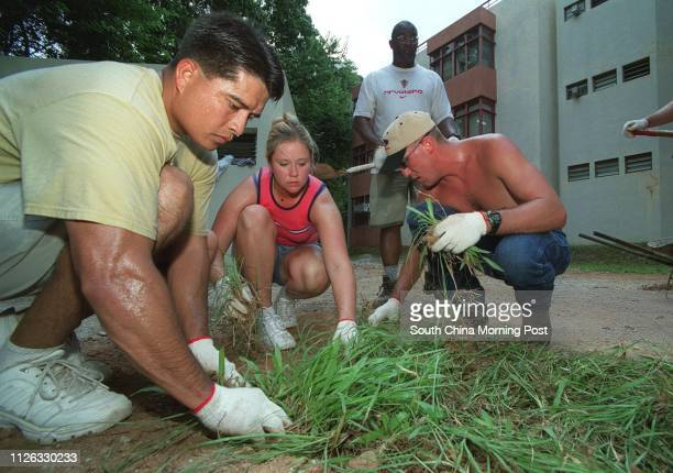 FCC Edward Garcia HM3 Amanda Wardleigh and DC2 Anthony Duncan US Navy sailors from the USS Curtis Wilbur help cut grass clear mud and trim trees on...