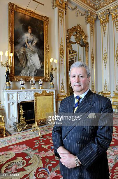 Edward Griffiths Deputy Master of the Household stands in front of a painting of Queen Alexandra wife of Edward VII by Francois Flameng in the White...
